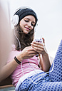Portrait of smiling teenage girl holding smartphone hearing music with headphones - UUF001599