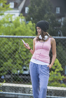 Portrait of smiling teenage girl with smartphone and headphones leaning at wire fence - UUF001633