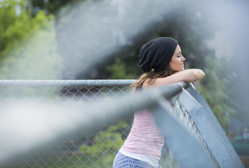 Portrait of smiling teenage girl wearing wool cap leaning on a wire fence - UUF001635