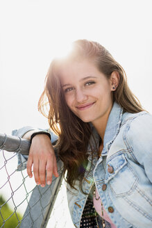Portrait of smiling teenage girl wearing jeans jacket leaning on a fence - UUF001640