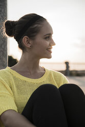 Profile of smiling teenage girl sitting on a parking level at evening twilight - UUF001647
