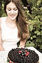 Portrait of young woman with chocolate berry cake - FCF000402