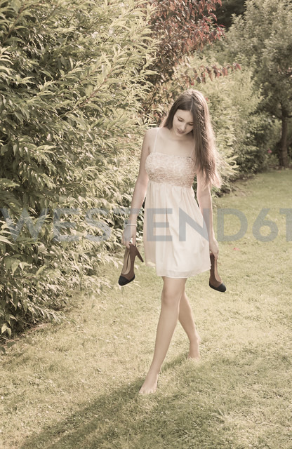 Young woman walking barefoot on meadow in the garden - FCF000406