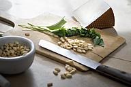 Chopped ramson, pine nuts and Pecorino cheese on chopping board - ASF005467