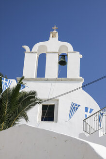 Greece, Cyclades, Naxos, View to bell tower of a church and Greek pennants on a line - KRPF000836