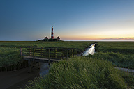 Germany, Schleswig-Holstein, North Sea Coast, View of Westerheversand Lighthouse after sunset - RJF000252