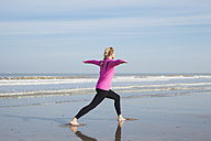 Belgium, Flanders, woman doing yoga exercise on the beach - GW003527