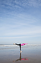 Belgium, Flanders, woman doing yoga exercise on the beach - GW003532