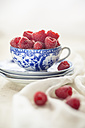 Raspberries in and around tea cup - SBDF001184
