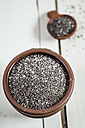 Earthenware dish and wooden spoon of organic black chia, Salvia hispanica, on white wood - SBDF001164