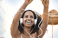 Happy young woman with headphones outdoors - KD000396