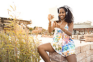 Happy young woman with headphones and digital tablet outdoors - KD000401