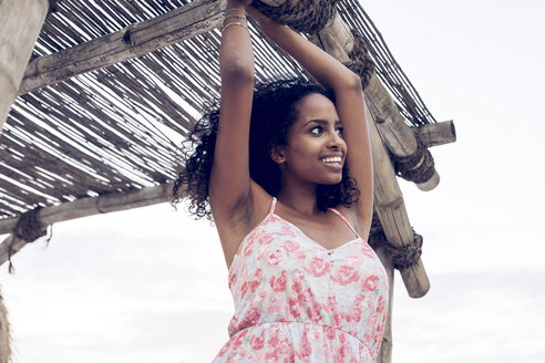Happy young woman at thatched hut - KD000412