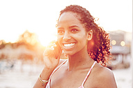 Happy young woman on cell phone at sunset - KD000473