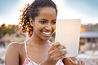 Happy young woman with digital tablet at sunset - KD000417