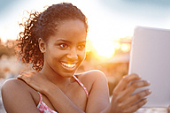 Happy young woman with digital tablet at sunset - KD000476