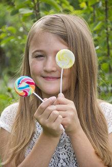 Portrait of girl holding lollipops - YFF000213