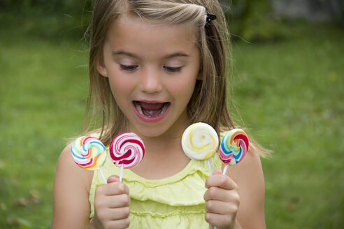 Portrait of girl holding lollipops - YFF000216