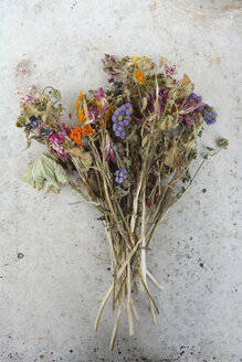 Germany, Bavaria, A bunch of withered field flowers and pink roses on a grey slab - AXF000715