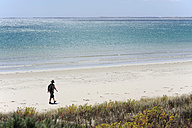 Australia, South Australia, Robe, woman walking on the beach - MIZ000552
