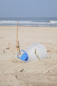 Belgium, empty plastic bottle lying on sandy beach at North Sea coast - GW003128