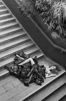 Woman wearing dress made from bin bags lying on stairs - FC000417