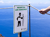 Spain, Canary Islands, La Palma, Fuencaliente, Sign and a hiker holding a safety rope - AM002694