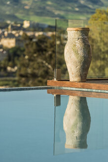 Morocco, Fes, vase standing at swimming pool of a hotel - KM001356