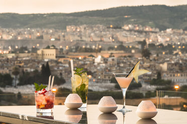 Morocco, Fes, three cocktails at the roof terrace of a hotel by sunset - KM001365