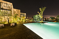 Morocco, Fes, view to lighted swimming pool at roof terrace of a hotel by night - KM001372