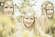 Portrait of three girls wearing floral wreaths - GDF000366