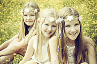Portrait of three girls wearing floral wreaths sitting on a flower meadow - GDF000391