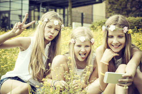 Portrait of three girls wearing floral wreaths taking a selfie on a flower meadow - GDF000389