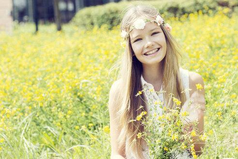 Portrait of a happy girl sitting on a flower meadow wearing flowers - GDF000386