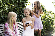Three girls spending their time with hairdressing - GDF000392