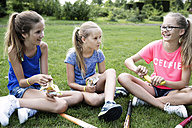 Three girls sitting on a meadow having a break - GDF000382