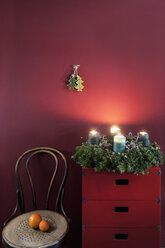 Advent wreath on sideboard at red wall - HHF004843