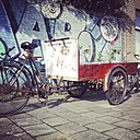 The Netherlands, North-Holland, Amsterdam, Cargo tricycle in front of a graffiti wall - HAW000450