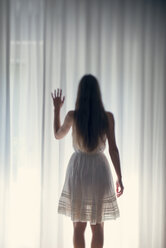 Mystical young woman standing in front of a white curtain, back view - BRF000571