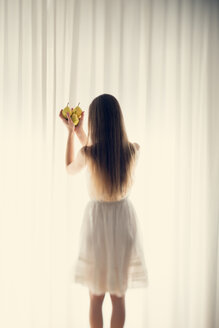 Young woman standing in front of a white curtain holding three pears in her hands, back view - BRF000583