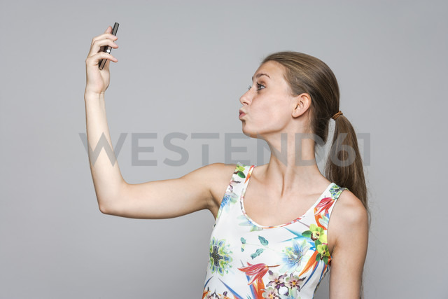 Young woman taking a selfie with smartphone in front of grey background - TCF004106