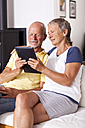Senior couple sitting on couch using digital tablet - JUNF000003