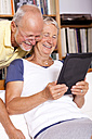 Senior couple at home having fun with digital tablet - JUNF000007