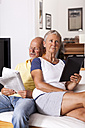 Senior couple sitting on couch reading newspaper using digital tablet - JUNF000014