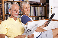 Senior couple sitting on couch reading newspaper using digital tablet - JUNF000015