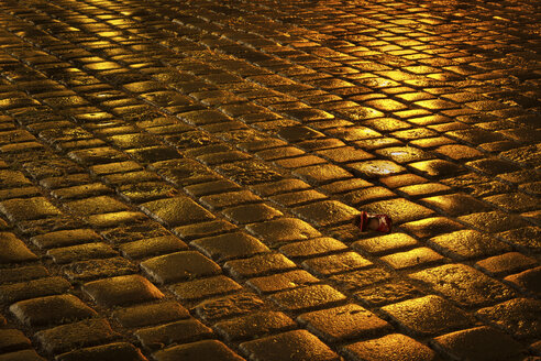 Lost red shoe lying on wet pavement by night - FCF000426