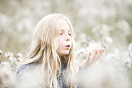 Portrait of girl standing in a field blowing seeds out off her hand - MAEF009021