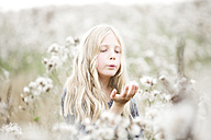 Portrait of girl standing in a field blowing seeds out off her hand - MAEF009023