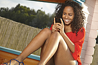 Smiling young woman reading SMS - KD000496