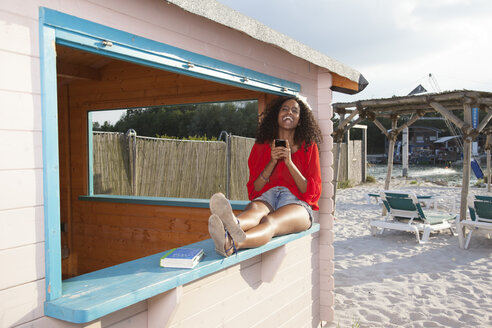Laughing young woman with smartphone at city beach - KD000497